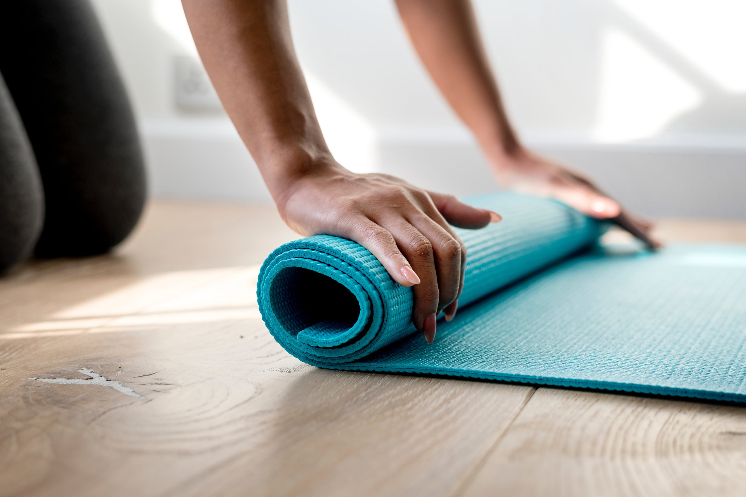 Image: A person unrolling a yoga mat on the ground. Photo:  rawpixel  on  Unsplash