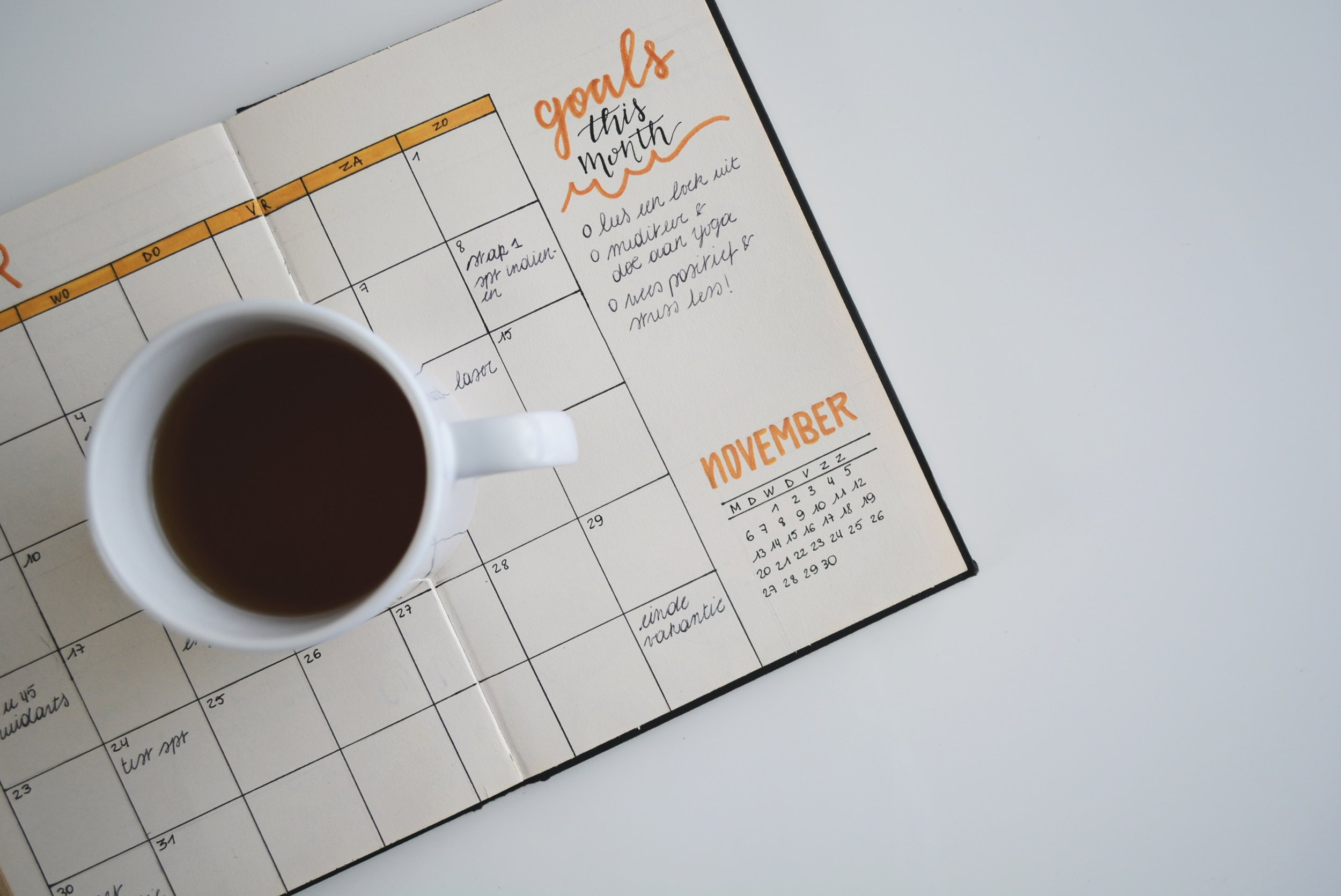 White ceramic mug with coffee on top of a planner.