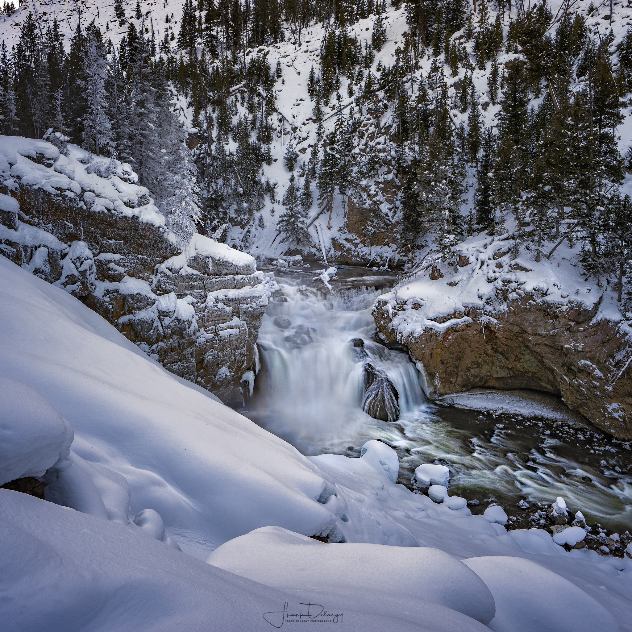 Something about a waterfall in the snow... the snow is whiter than the river usually.