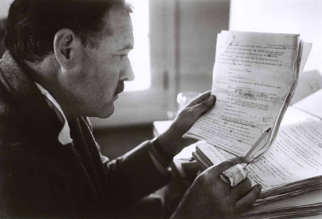 Ernest Hemingway stares intently at typewritten pages full of scribbled edits.