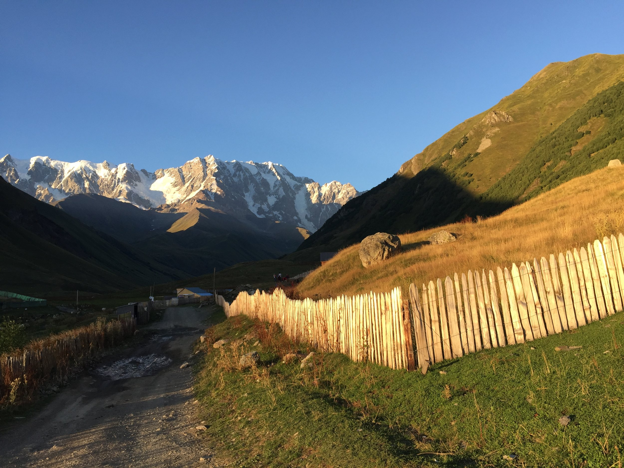 A rugged road traverses mountainous countryside near Ushguli, Georgia. A rickety wooden fence is lit by the evening sunlight.