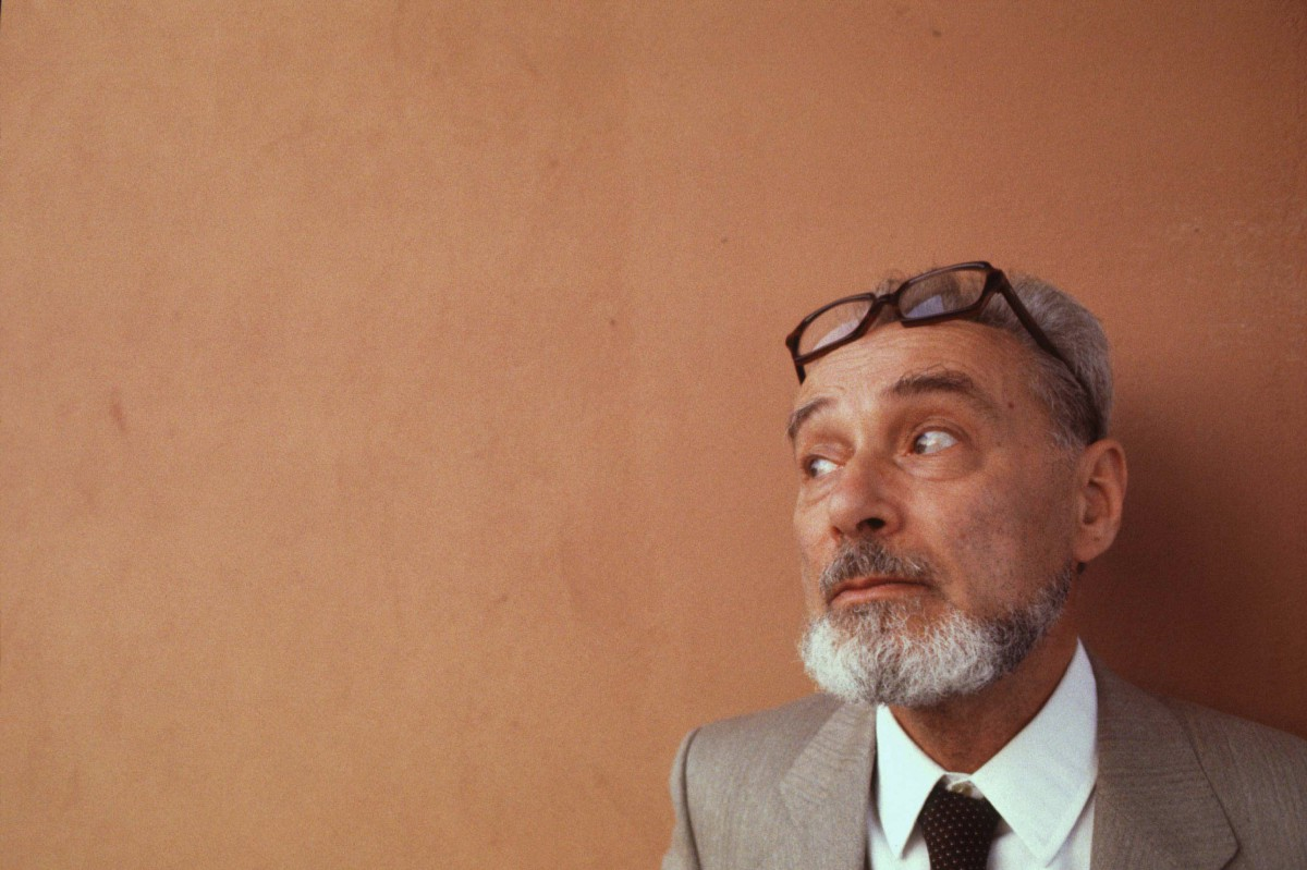 Primo Levi as a bearded old man, with spectacles on his forehead, glances sideways with a melancholy air.