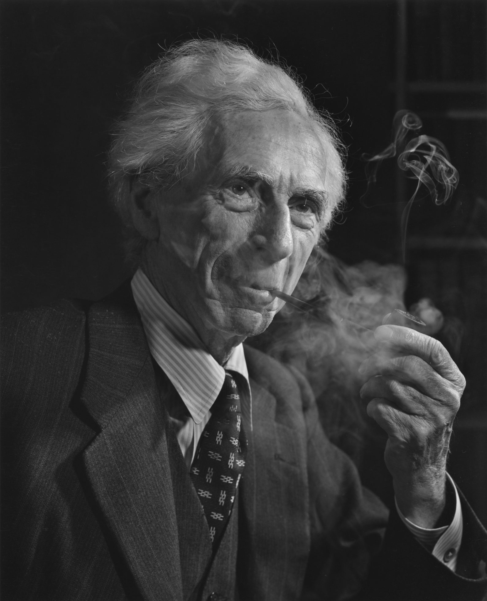 Betrand Russell as an old man, wearing a suit, smoking a pipe and looking cheerful.
