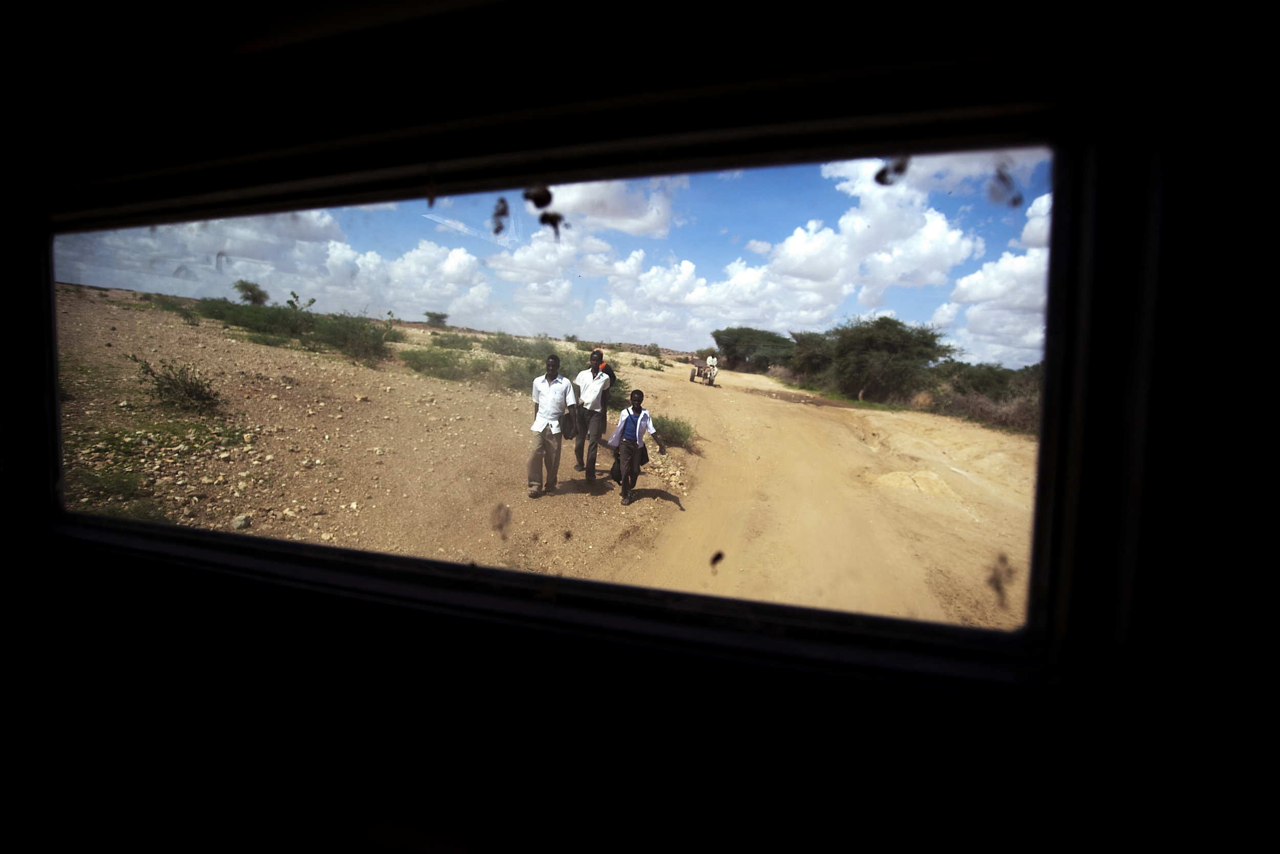 Pictured through the window of a vehicle from the African Union-United Nations Hybrid Operation in Darfur (UNAMID), displaced Sudanese travel on foot from Fata Burno to market in Kutum, North Darfur. UNAMID peacekeepers frequently patrol the road to shield the travellers from threats by Janjaweed militiamen. 02 August 2010 I North Darfur, Sudan  © UN Photo/Albert González Farran