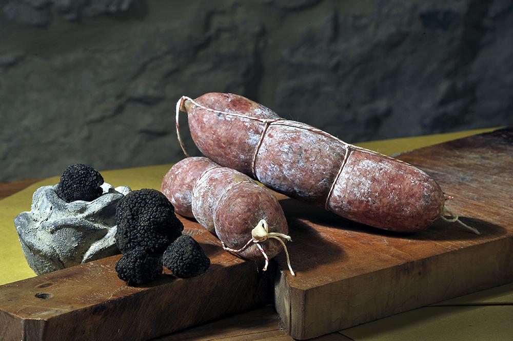 """CIAUSCOLO AL TARTUFO - Descrizione: Ciauscolo insaporito dal tartufo nero estivo di Norcia,salame tipico dell'entroterra della provincia di Macerata.Lavorazione: tagli selezionati di pancetta, spalla, guancia e carnette di maiale risultanti come rifilatura dei prodotti così detti """"nobili"""" (salami, prosciutti, lonze ecc.), tartufo,sale, vino, aglio e pepe.Salame la cui particolarità è la morbidezza e la spalmabilità, ottimo per una merenda o un antipasto squisito se spalmato tipo una marmellata su del pane bruscato."""