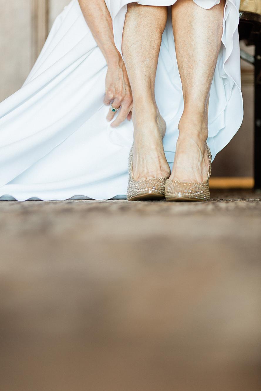 Dallas Wedding photographer Las Colinas Country Club wedding details bride putton on shoes Kate Marie Portraiture.png