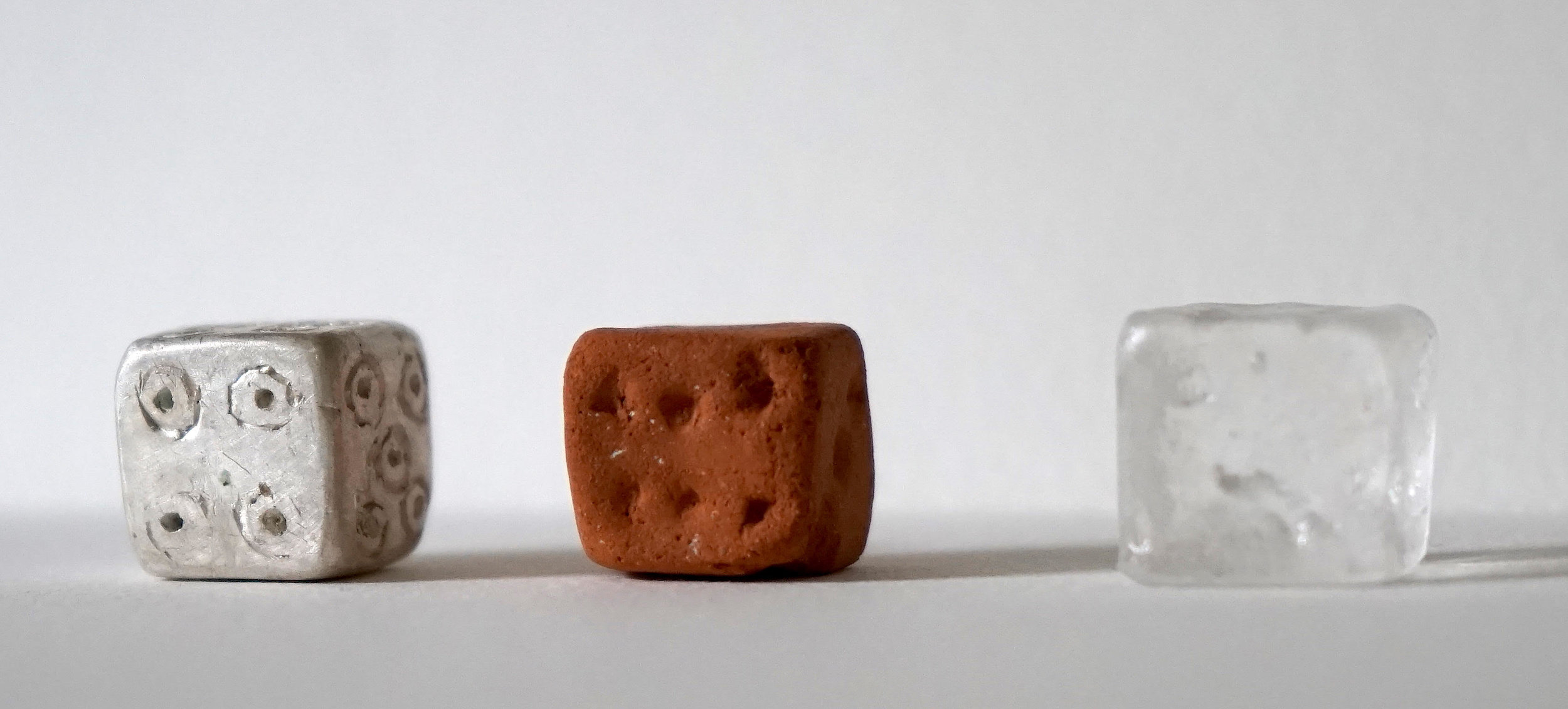 """""""Dice"""" - Materials: fired clay dug from a riverbed in Peru, lost wax silver cast, and kiln cast glass"""