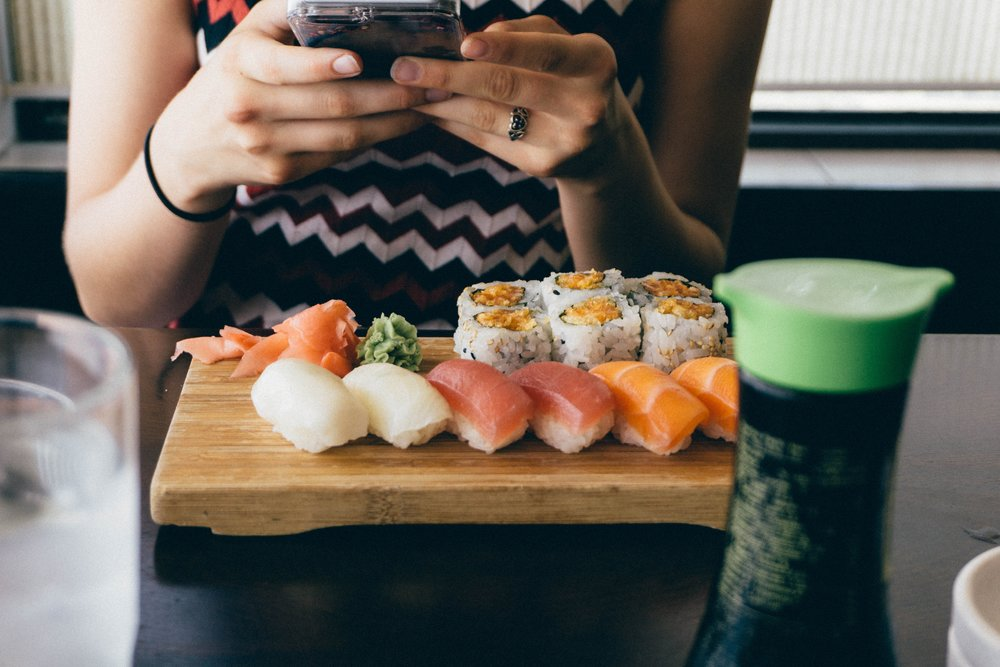 Woman photographing sushi Photo by  j  on  Unsplash