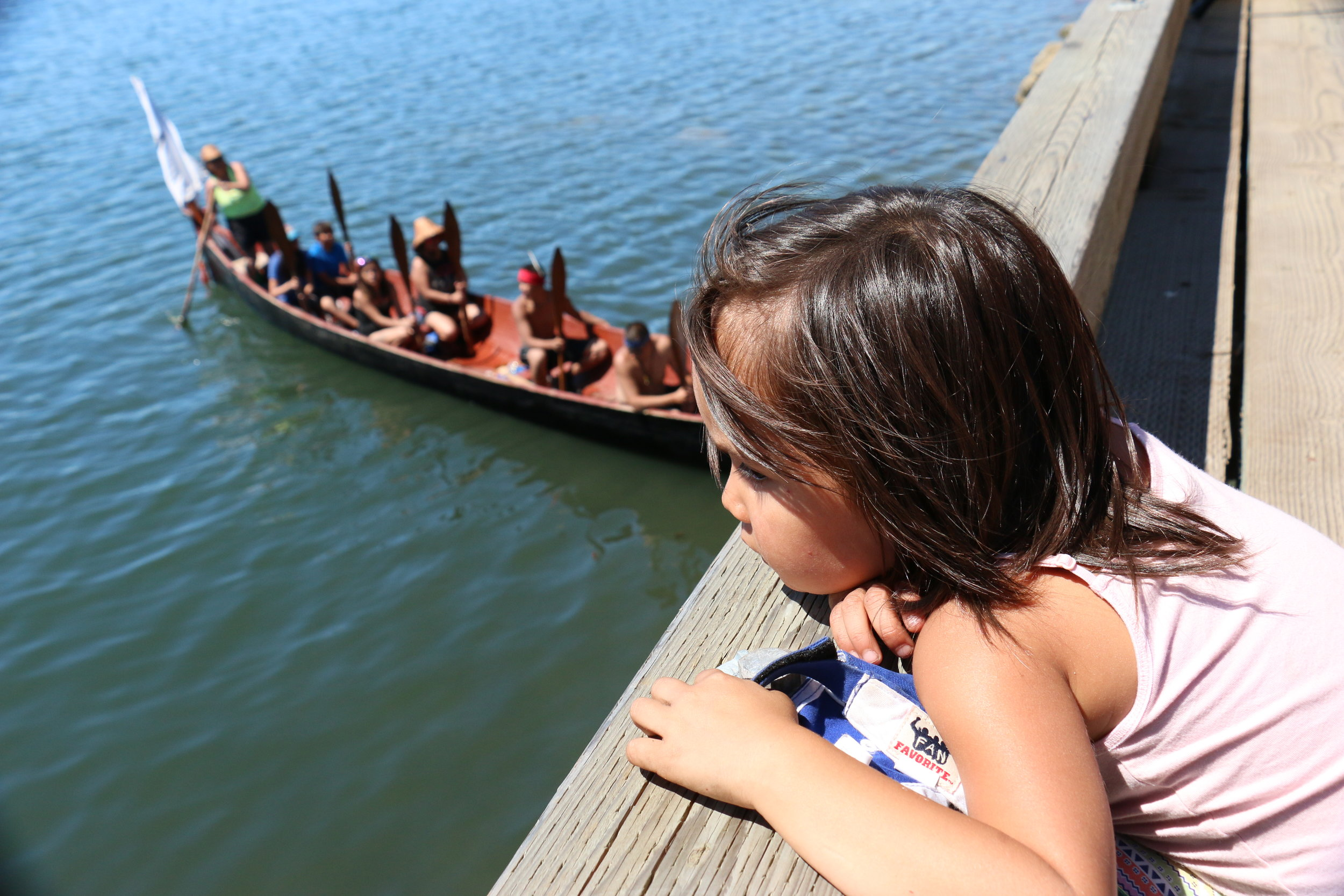 A young girl playing on the dock pauses to watch the canoes arrive in Esquimalt Harbour. (Julian Brave NoiseCat)
