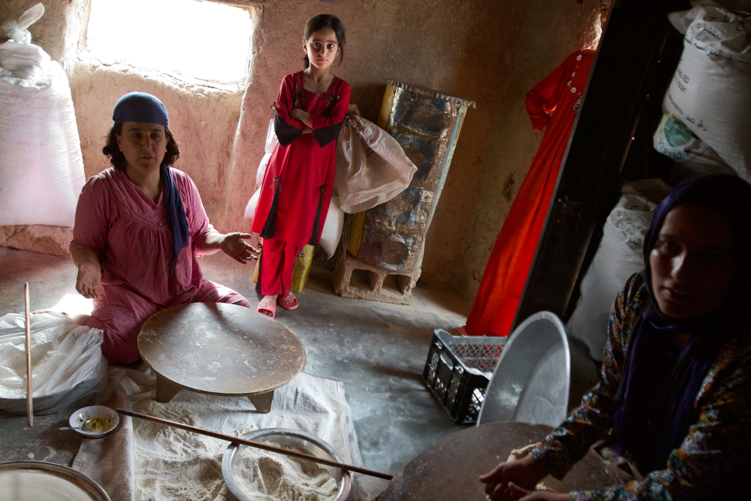 """In Kani Sard, a village two miles from Jarmo (where wheat was domesticated around 8,000 B.C.), women make bread with bags of flour marked """"Pakistan"""". Along with lack of water and limited agricultural land, dwindling government support has threatened local farming. More than half of Kani Sard's population has left for the cities in the past few years."""