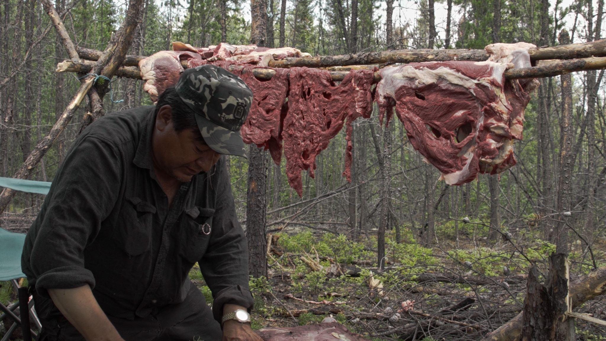 Freddie Throassie hangs moose meat to dry.