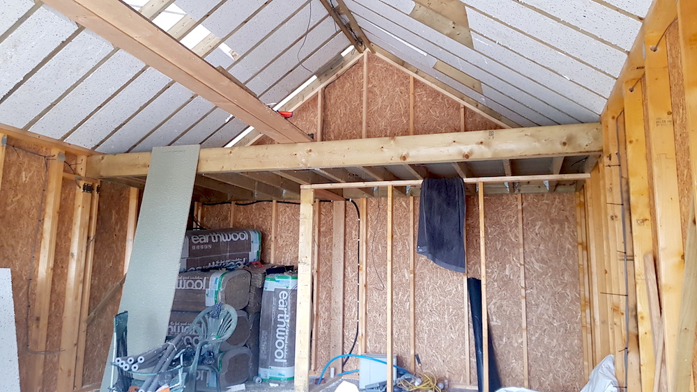 The roof insulation goes in, the mezzanine is up, and the structure for the shower room and kitchenette are coming together.