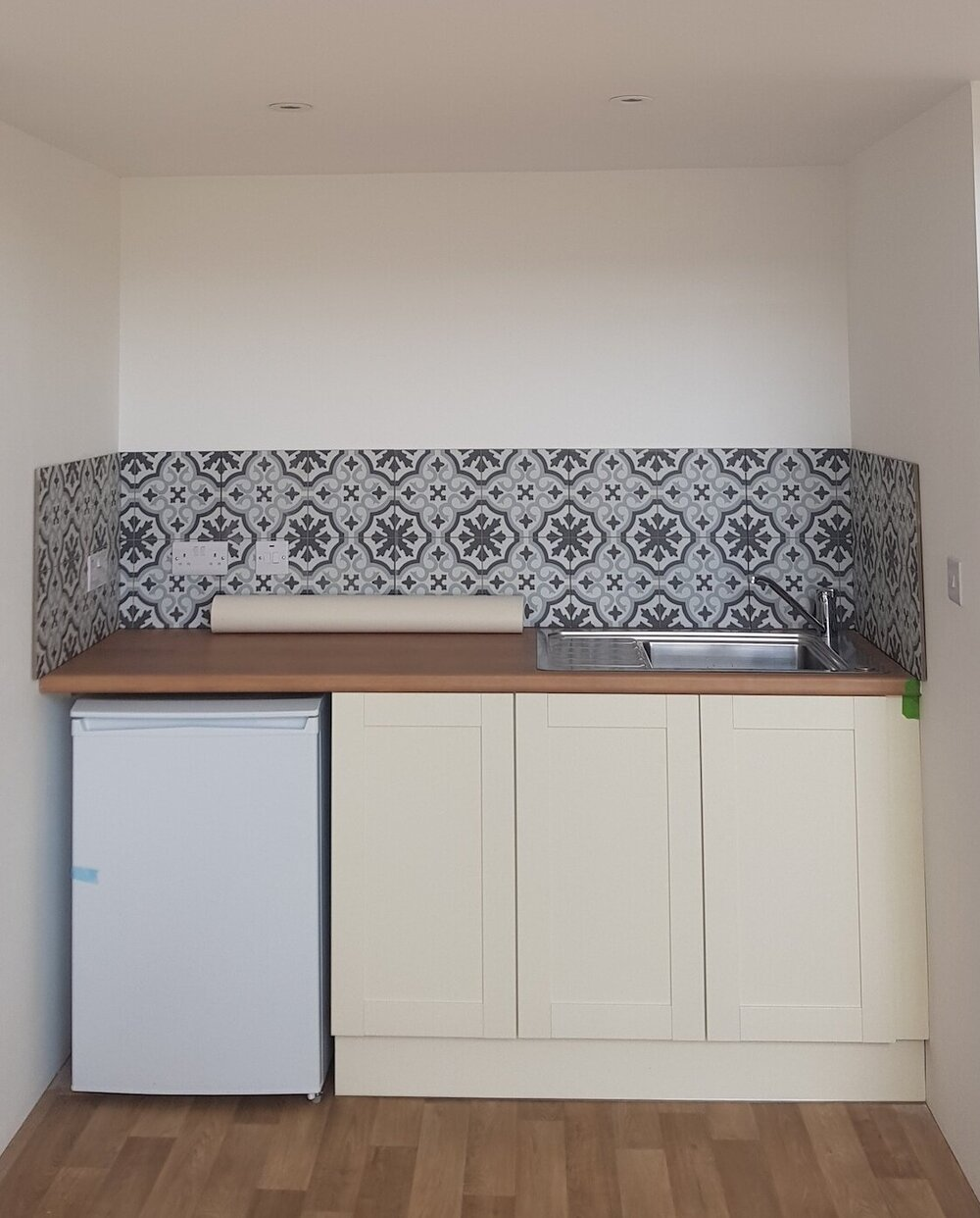 The tiny kitchenette sits in a little alcove at the back of the studio. A simple run of three cupboards, an under counter fridge with freezer compartment, and more leftover tiles from the barn renovation give it character while being functional. Perfect for essential coffee and tea while painting, and adaptable {with microwave and shelf above, added later - also cupboard knobs!} for longer term use. There's a little hot water tank in one of the cupboards too.