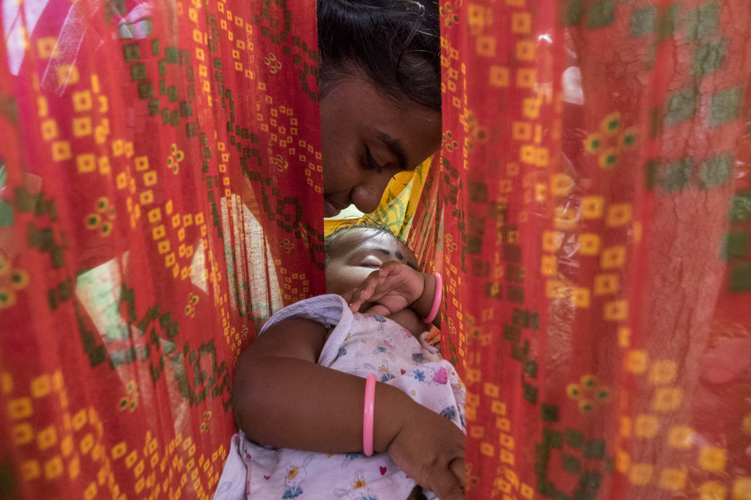 Bhuvaneshwari. P - The red cotton saree hangs from the Neem tree and cradles Dhanshika, an 8-month baby girl. Her sister kisses the baby as she sleeps in Anna Nagar.