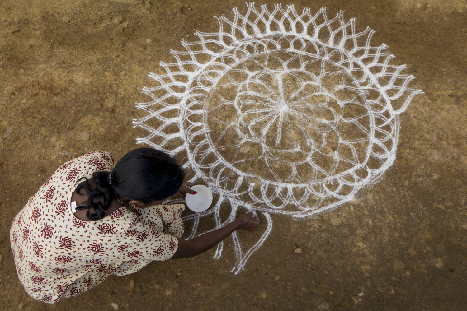Karthika. S - Hindu women practice Rangoli on their front doorstep to add beauty to their homes. Rangoli is made from rice powder and starts with symmetrical lines and dots. From that base, women can pick colours and make their own designs.