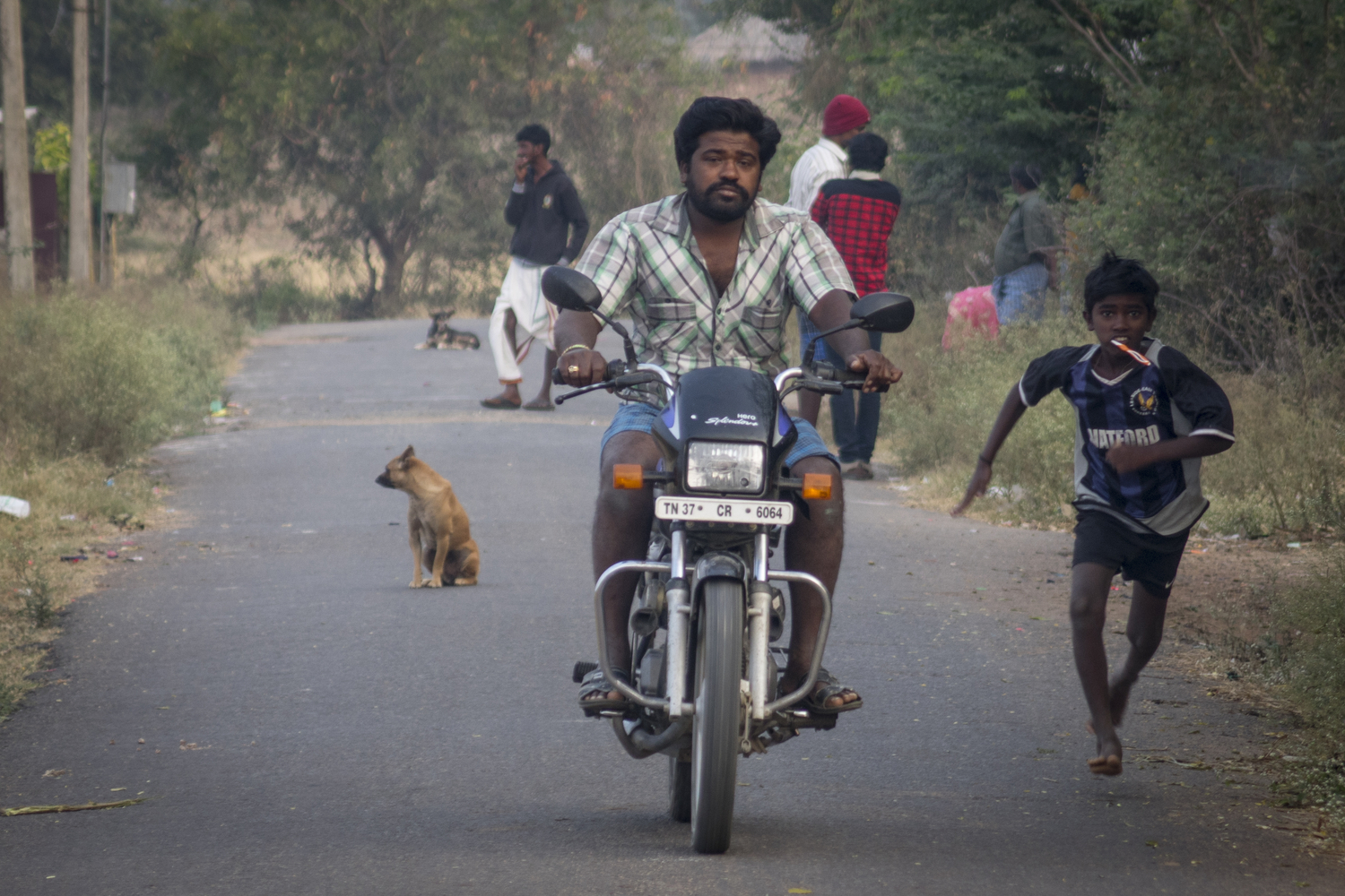 Mohanapriya. P - A man on a motorbike and a boy named Shriram race each other. They do this every morning for fun.