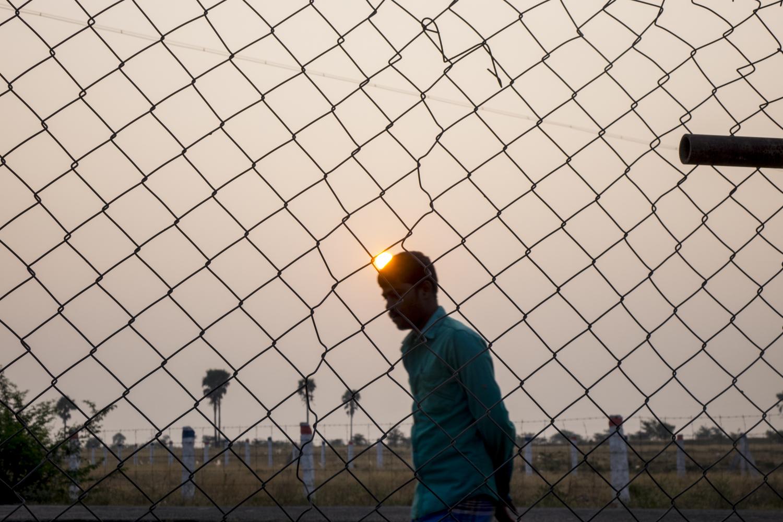 A man walks during the sunset in Kalaignar Nagar. His name is Guna. He has very powerful strength.  Kishore. S