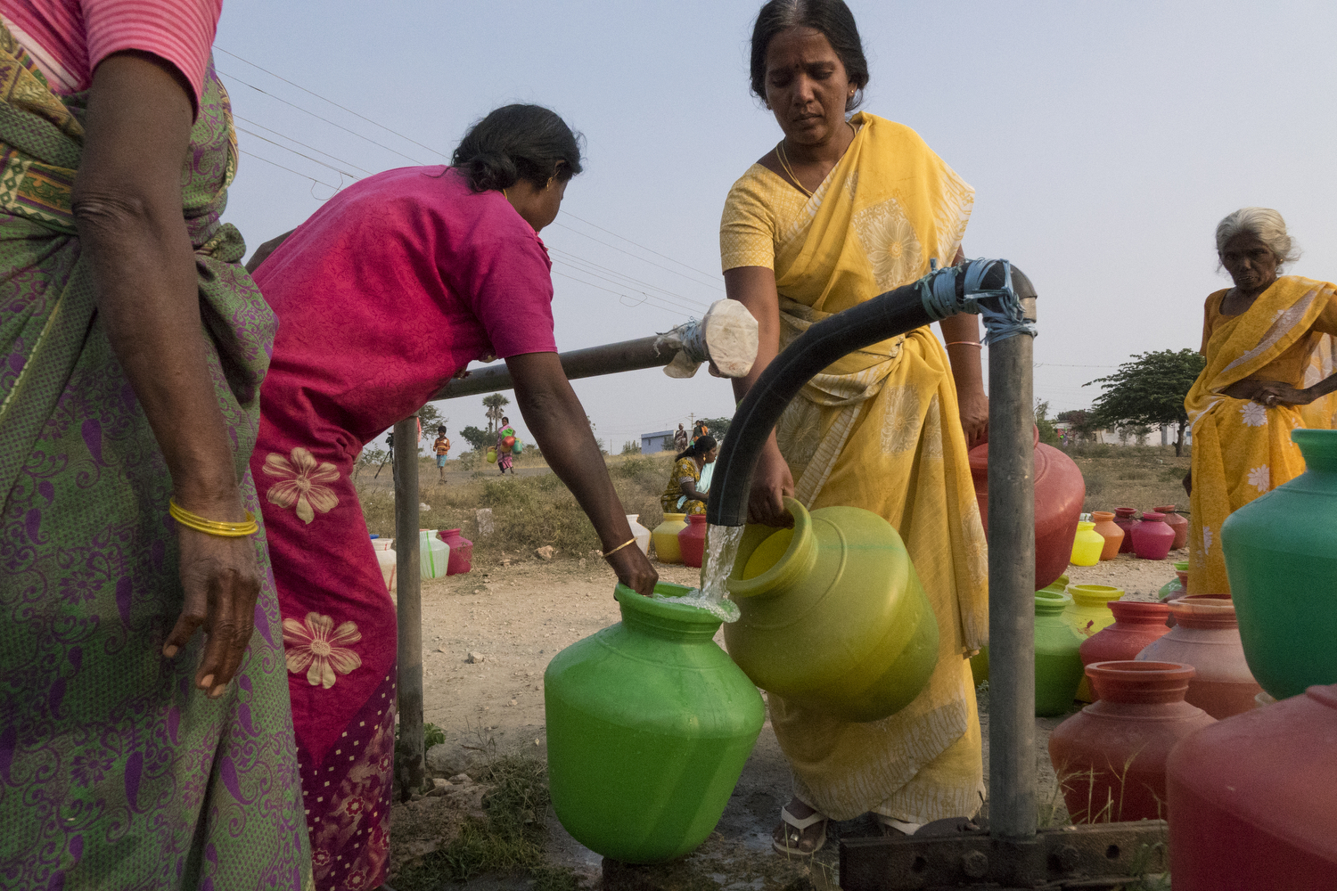 Women collect cooking water from the borewell tap in Anna Nagar settlement. The tap turns on every day at 4pm and is half a kilometre away from the settlement houses. Each house gets four pots of water.  Bhuvaneshwari. P