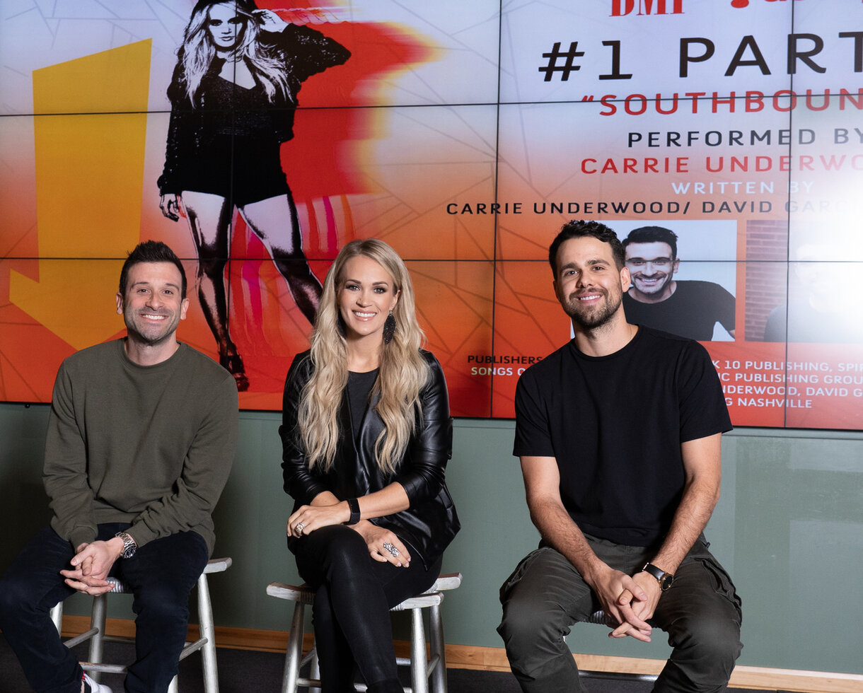"Carrie Underwood celebrates her No. 1 hit, ""Southbound,"" with her co-writers David Garcia and Josh Miller. (Steve Lowry/BMI)"