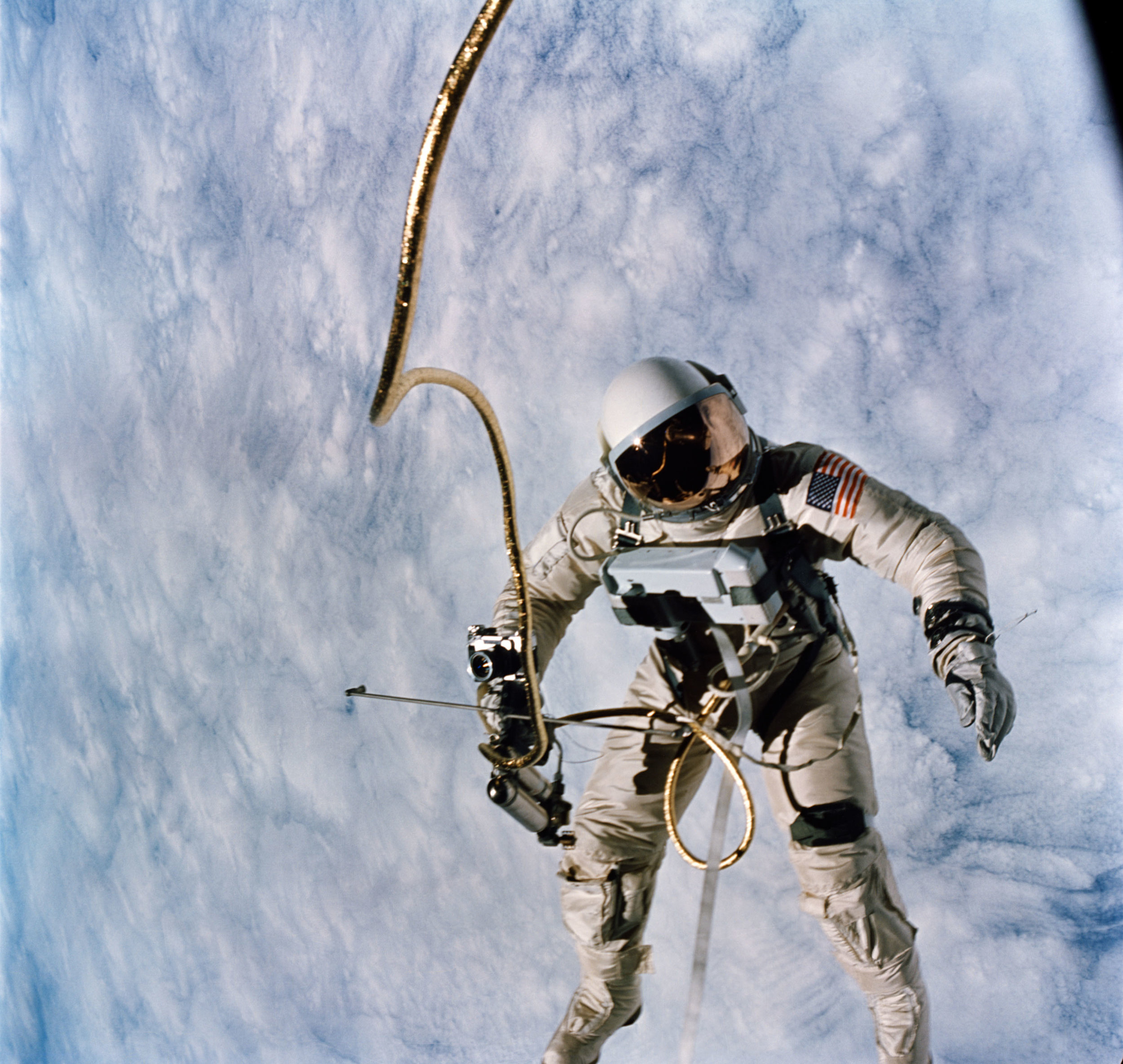 Clasping the cold-gas maneuvering gun in his right hand, and trailed by a snake-like tether, Ed White tumbles over a cloud-speckled Earth during the United States' first EVA. Photo Credit: NASA