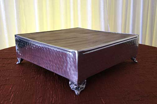 "Stainless Steel Cake Stand  with Rustic Wood Surface  13 1/2"" x 13 1/2"" x 5 1/4"" tall $20.00 17 1/2"" x 17 1/2"" x 6 1/4"" tall $25.00 21 1/2"" x 21 1/2"" x 6 1/4"" tall $35.00"