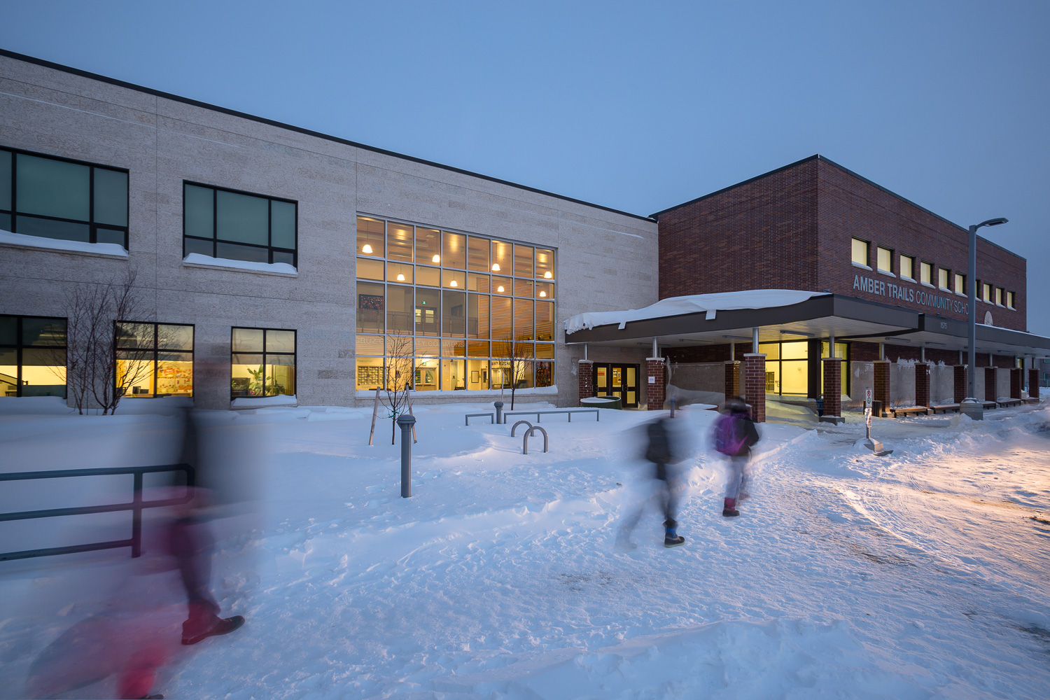 Amber Trails Community School, exterior photo of school at dusk with people walking by / Photo:  Lindsay Reid