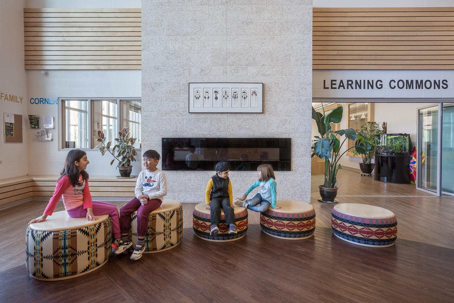 Amber Trails Community School, interior photo of main lobby fireplace detail with children sitting / Photo:  Lindsay Reid