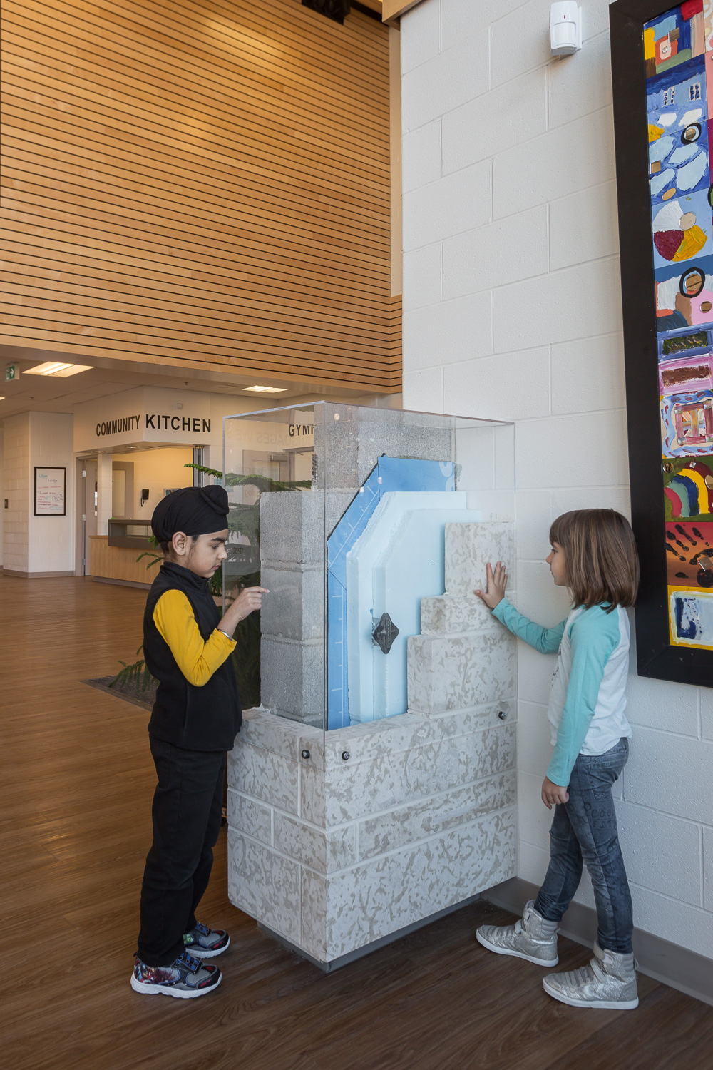 Amber Trails Community School, interior photo of main lobby with children looking at exposed wall systems / Photo:  Lindsay Reid