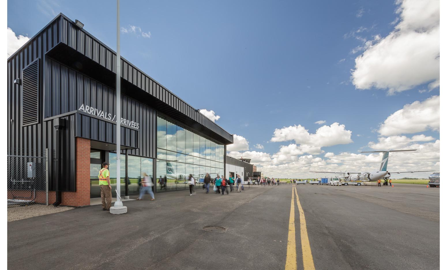 Brandon Municipal Airport, exterior photo of arrivals hall with passengers disembarking a plane / Photo:  Lindsay Reid