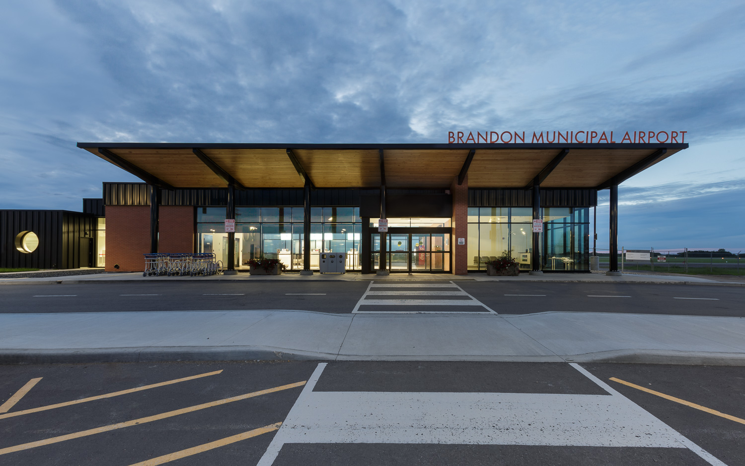 Brandon Municipal Airport, exterior photo of building entrance at dusk / Photo:  Lindsay Reid