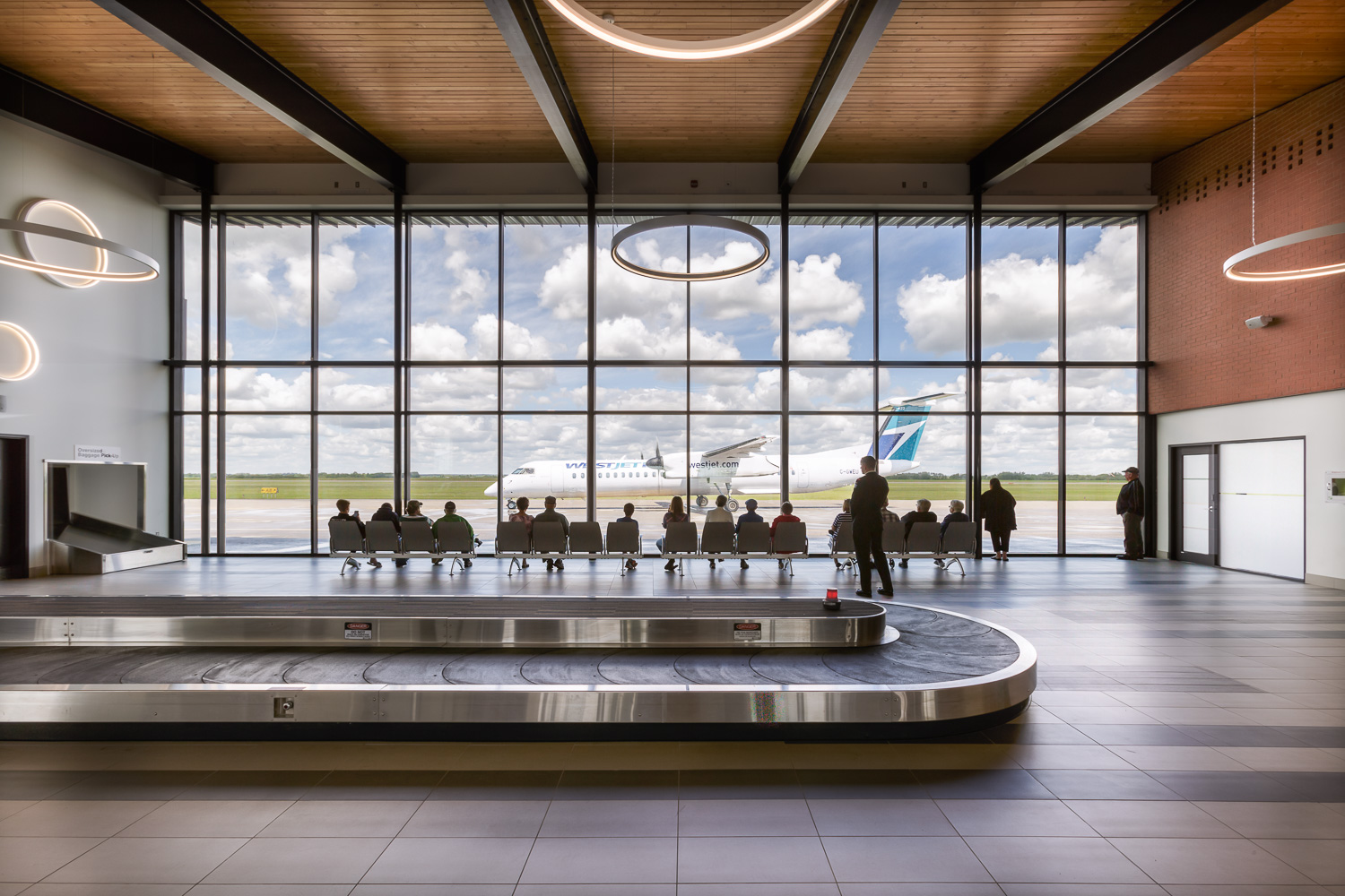 Brandon Municipal Airport, interior photo of Arrivals Hall with people watching a plane taxi by outside / Photo:  Lindsay Reid