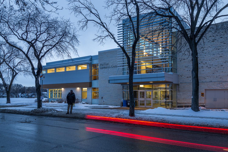 Centre de Santé Marcel A. Desautels, exterior photo of building from street with car driving by / Photo:  Lindsay Reid