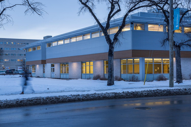 Centre de Santé Marcel A. Desautels, exterior photo of building at dusk with person walking by / Photo:  Lindsay Reid
