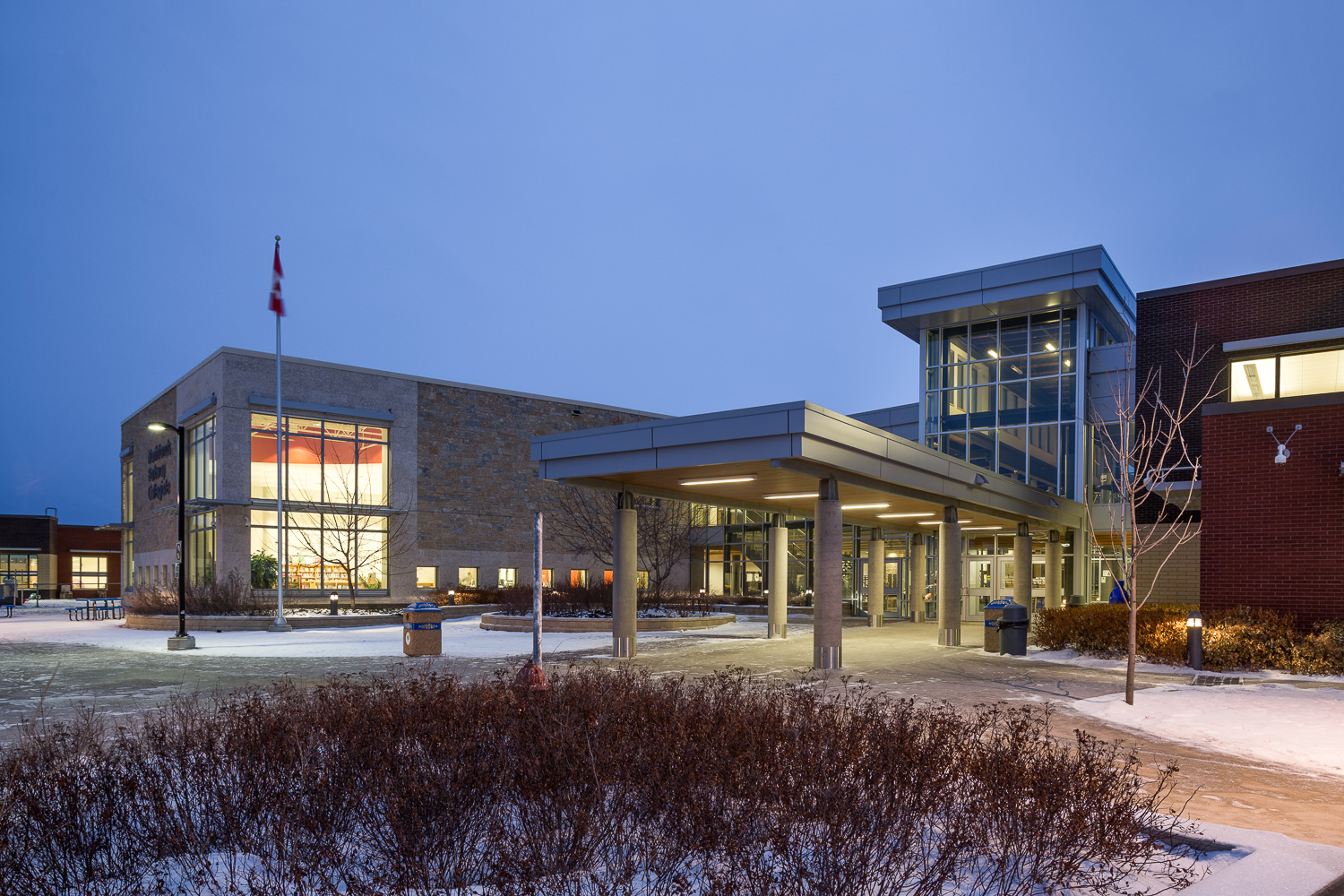 Northlands Parkway Collegiate, exterior photo of the building entrance at dusk / Photo:  Lindsay Reid