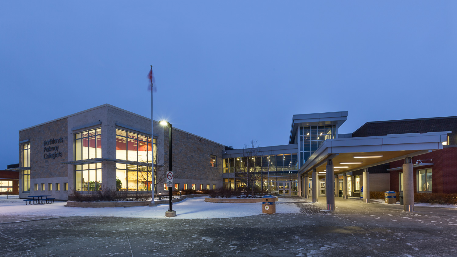 Northlands Parkway Collegiate, exterior photo of the building entrance and library at dusk / Photo:  Lindsay Reid