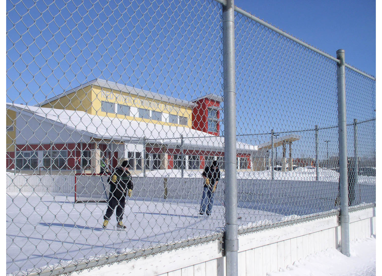 Red River Community Centre, exterior photo of building in winter with kids playing hockey in foreground