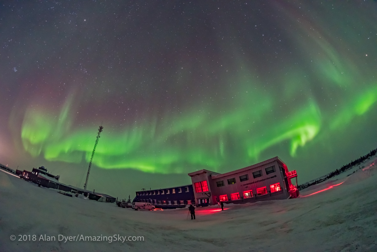 Swirls of aurora in the northern sky over the Churchill Northern Studies Centre, in Churchill, Manitoba, with members of the Learning Vacations tour group out front taking photos. The building is in red light mode for night sky viewing. Cassiopeia is at left; Polaris is at centre. 