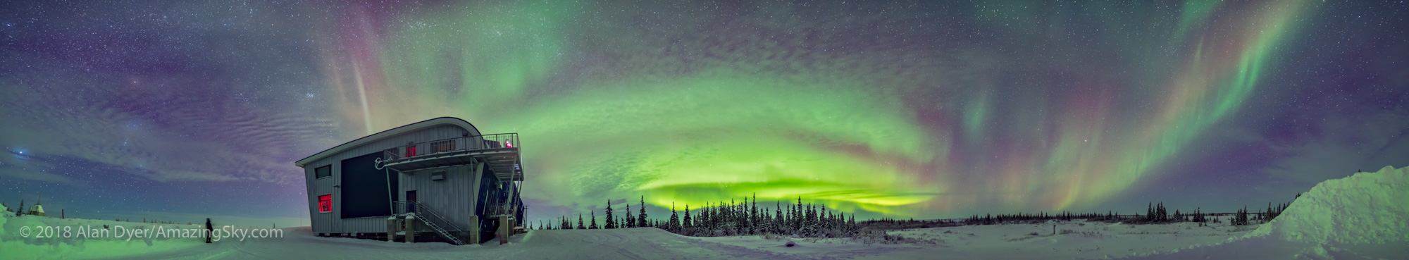 A 270° panorama from southwest to northeast taking in the full sweep of the auroral arcs this night, January 29, 2017 at the Churchill Northern Studies Centre, on the shore of Hudson Bay in Churchill, Manitoba. Sirius and Orion are at far left. The Pleiades is over CNSC. Arcturus is at far right. A lone aurora observer stands at left. Someone is also on the second floor deck. A bit of an isolated arc is at right to the east. This is a stitch of 11 segments, each 10 seconds at f/2 with the Sigma 20mm Art lens and Nikon D750 at ISO 3200. Stitched with Adobe Camera Raw.