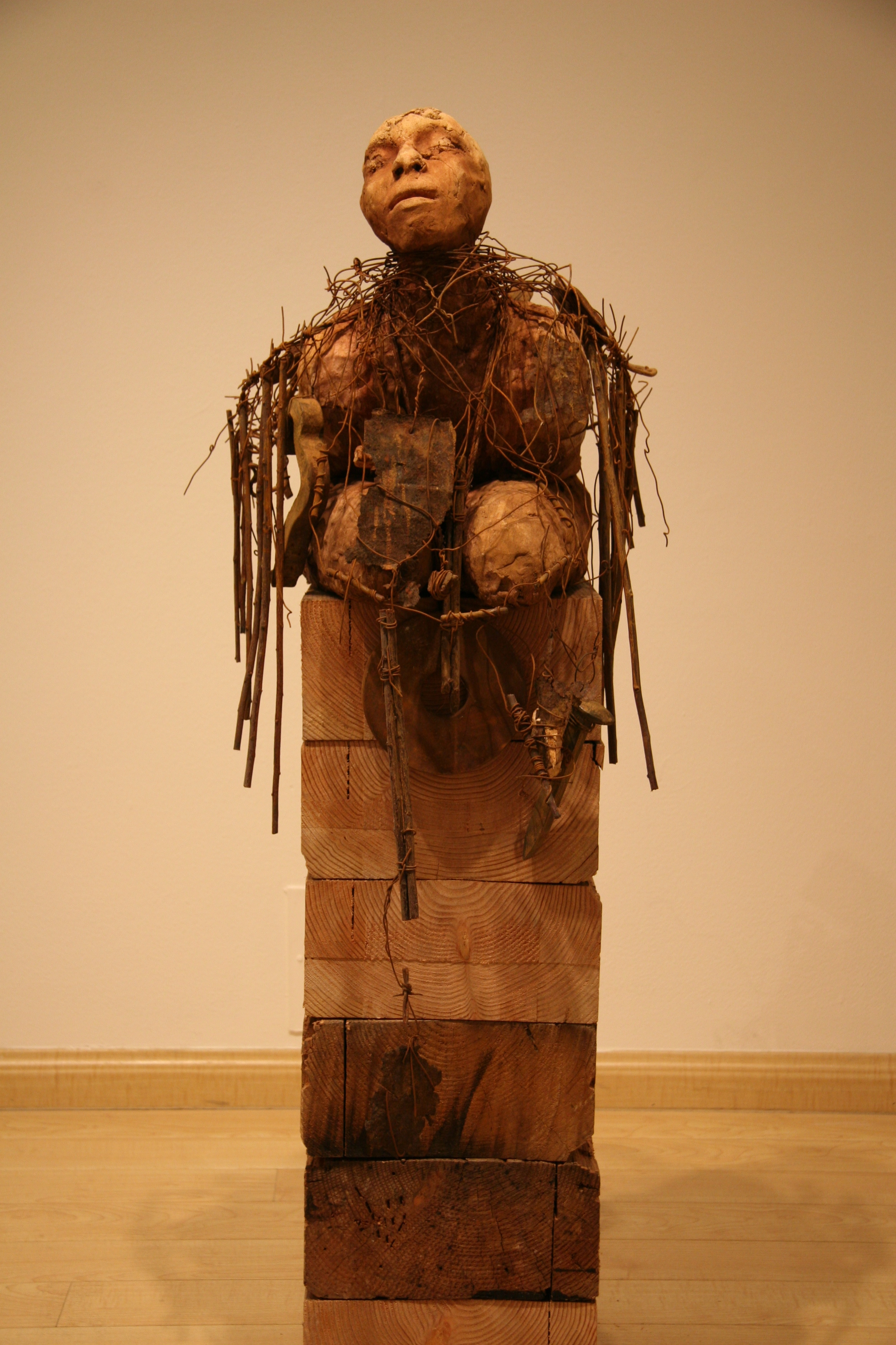 Unconscious forgetfulness   2006-2007  Ceramic, wire, branches with rusted objects  50 x 17 x 24   The figure is weighed down and entangled in detritus of the past that is evidence of suffering that leads to renewal.