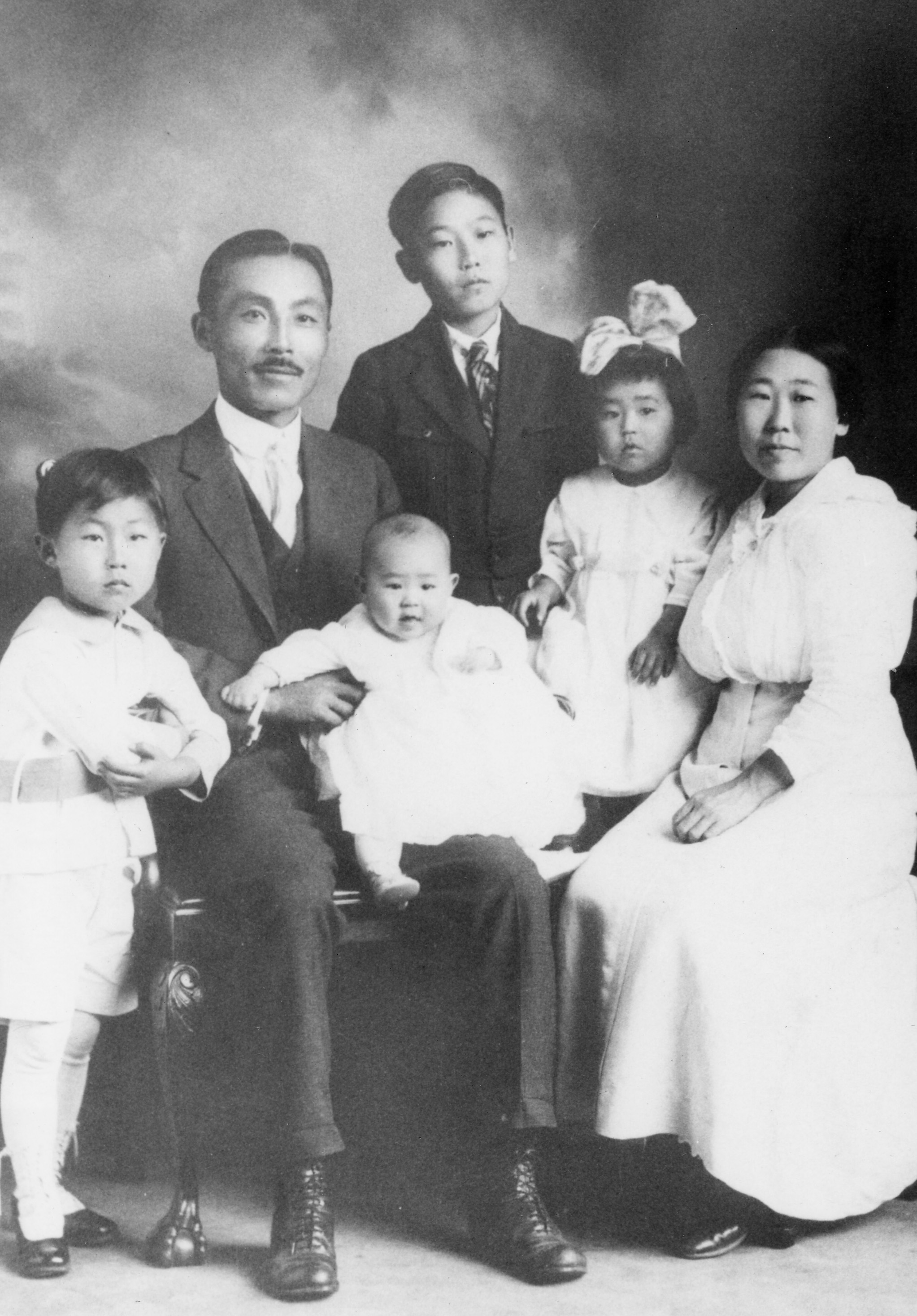 Susan (with hair bowtie) seated with her family circa 1917.