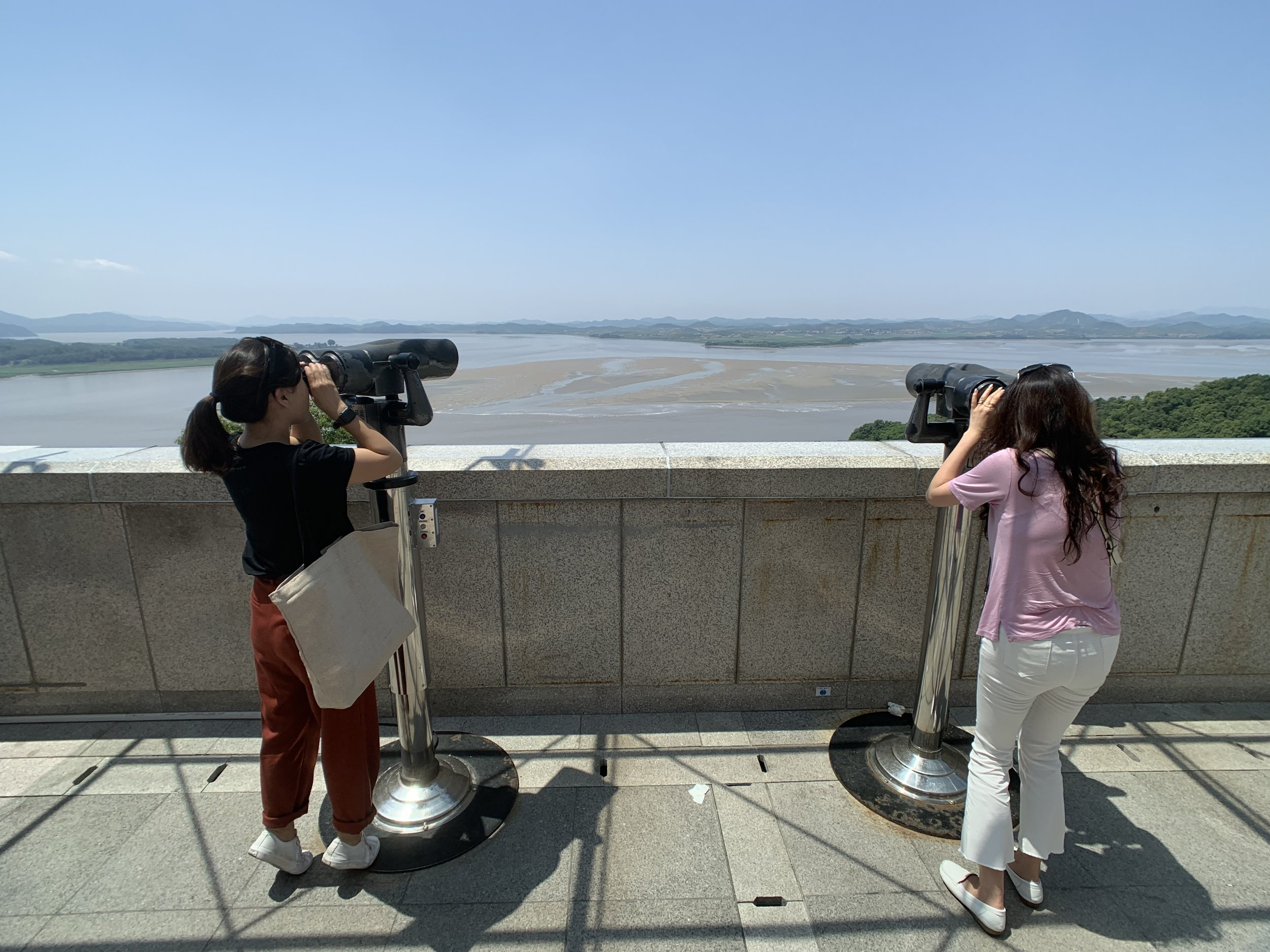 Looking at North Korea across the waters through the binoculars