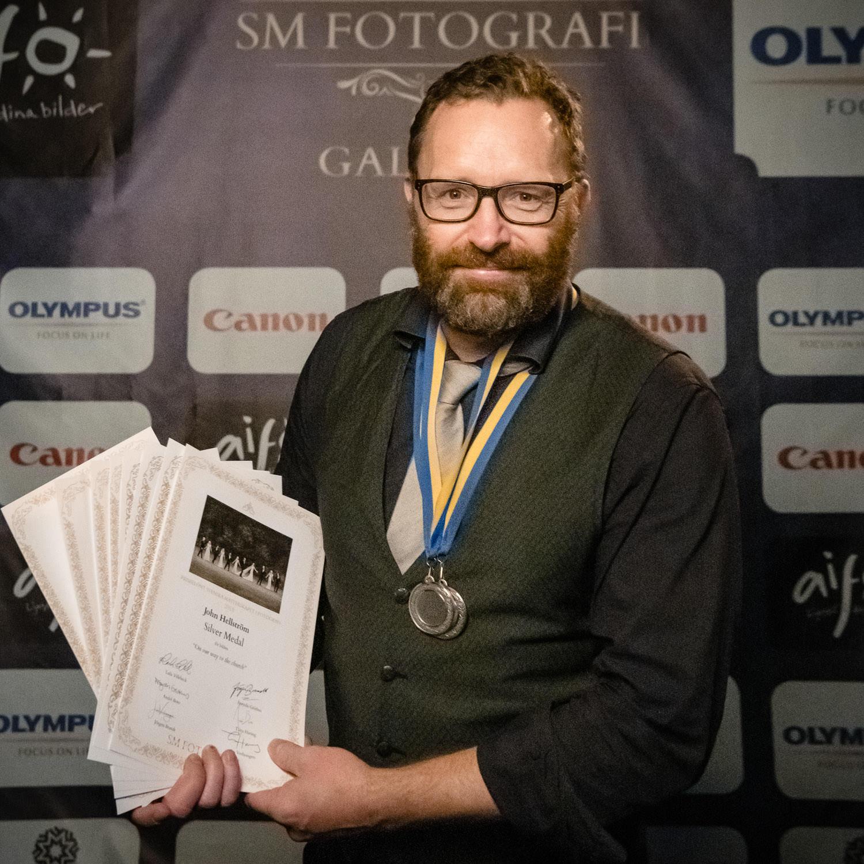 Fotograf John Hellström med sju utmärkelser och två silvermedaljer från SM i fotografi 2018. Foto: Jenny Thörnberg.
