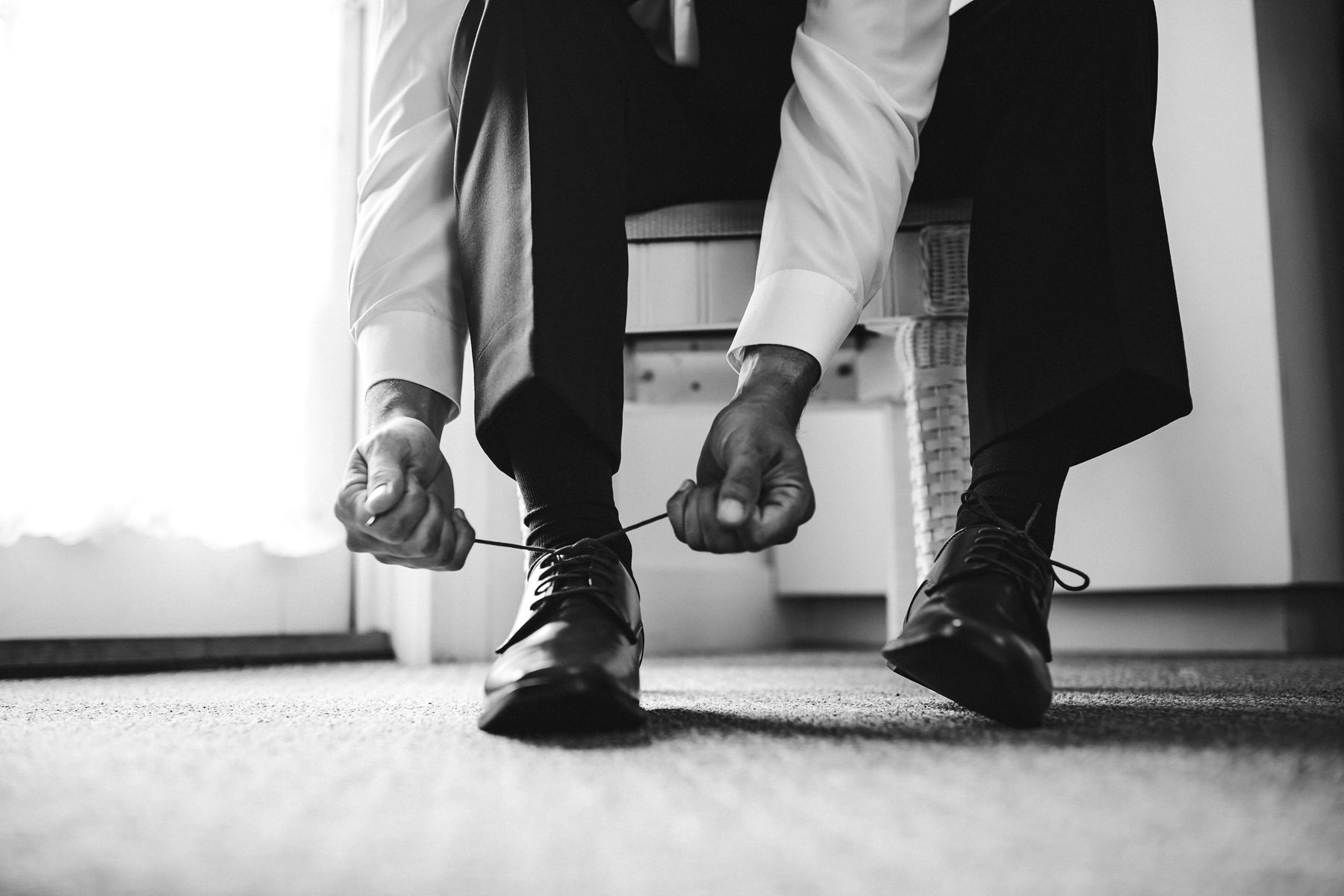 black-and-white-tying-shoes-groom-prep-wedding-day-tiny-house-photo.jpg