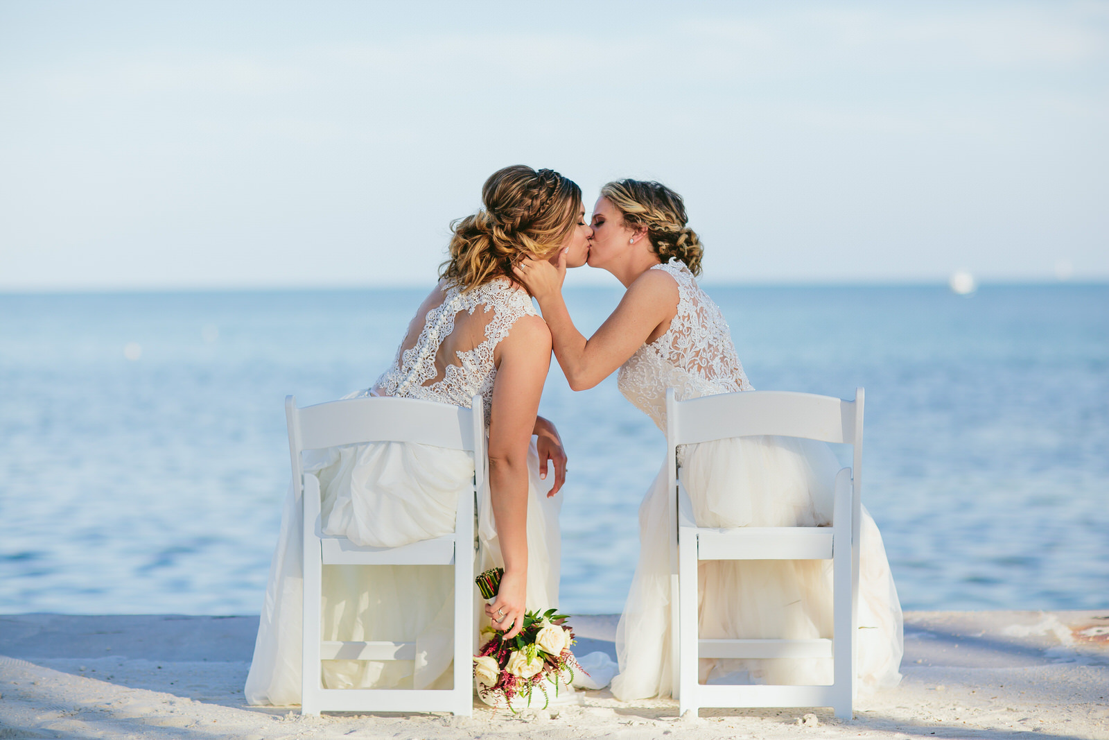 brides_sitting_kissing_sea_destination_lgbtq_weddings.jpg