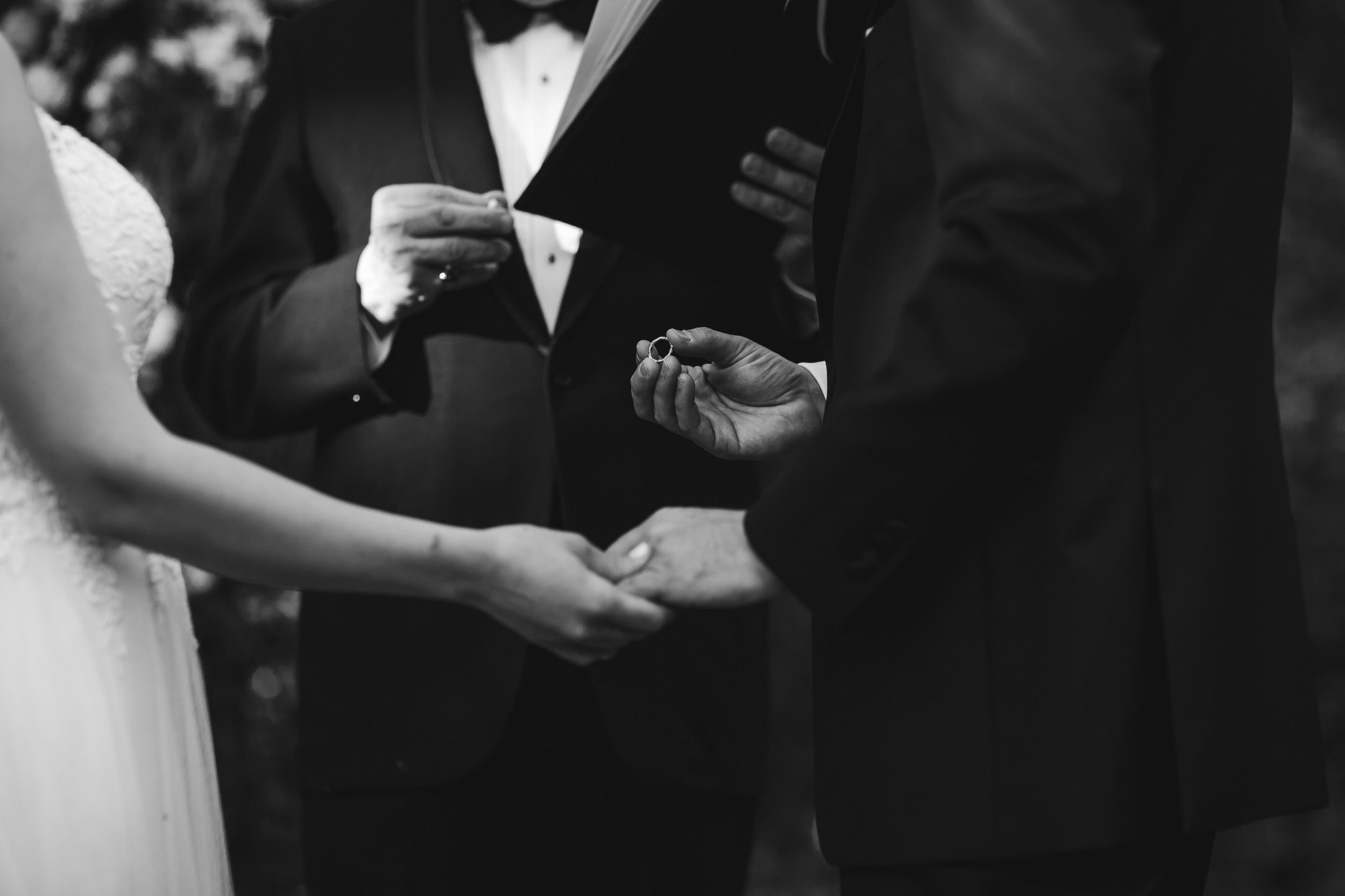 exchange_rings_tiny_house_photo_wedding_ceremony_black_and_white.jpg