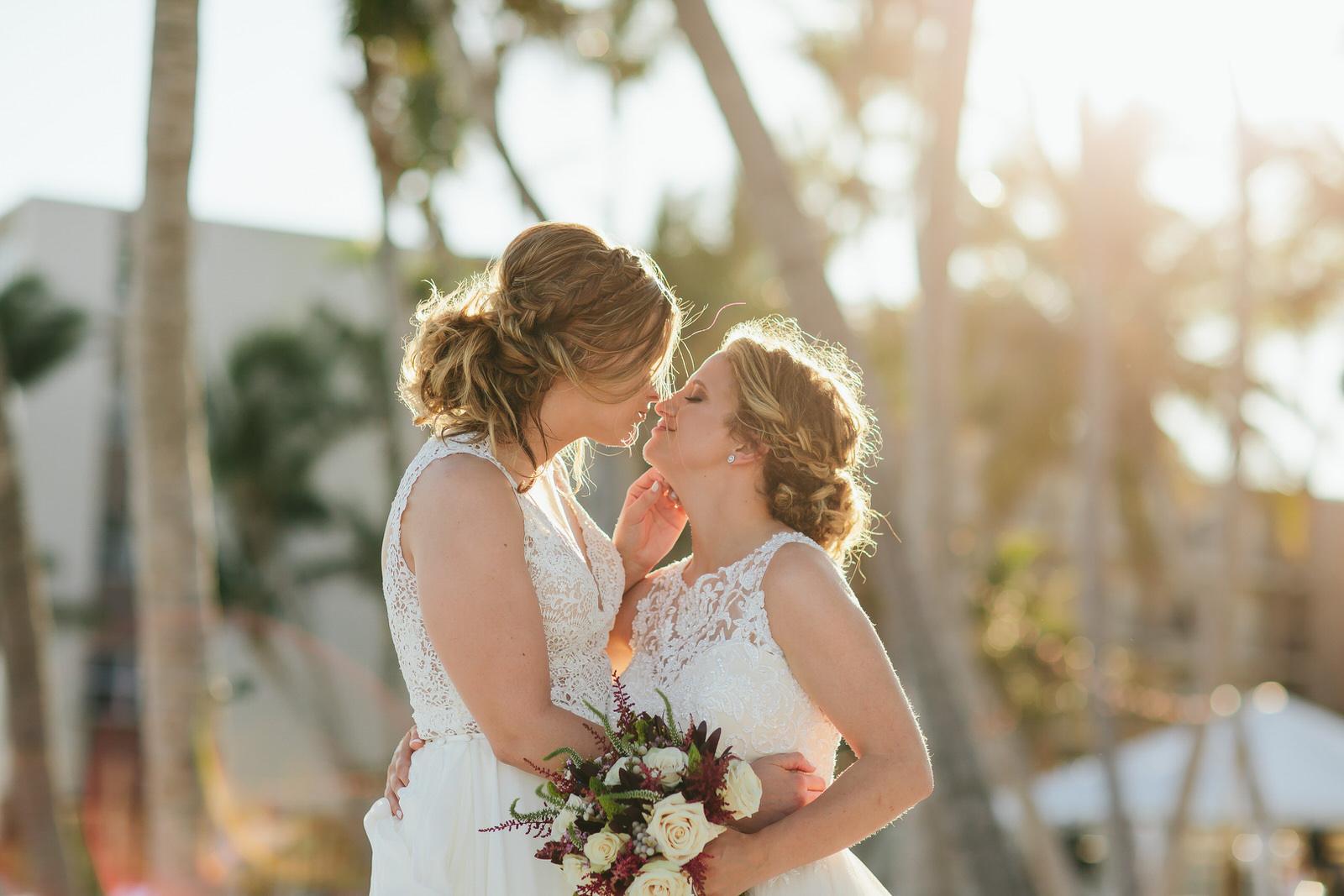 LGBTQ+ couple had a destination wedding at Amara Cay Resort in Islamorada, FL. Couple is kissing during golden hour on the beach.