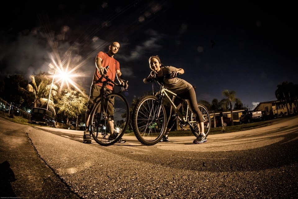 A man and woman on bikes in the street at night.