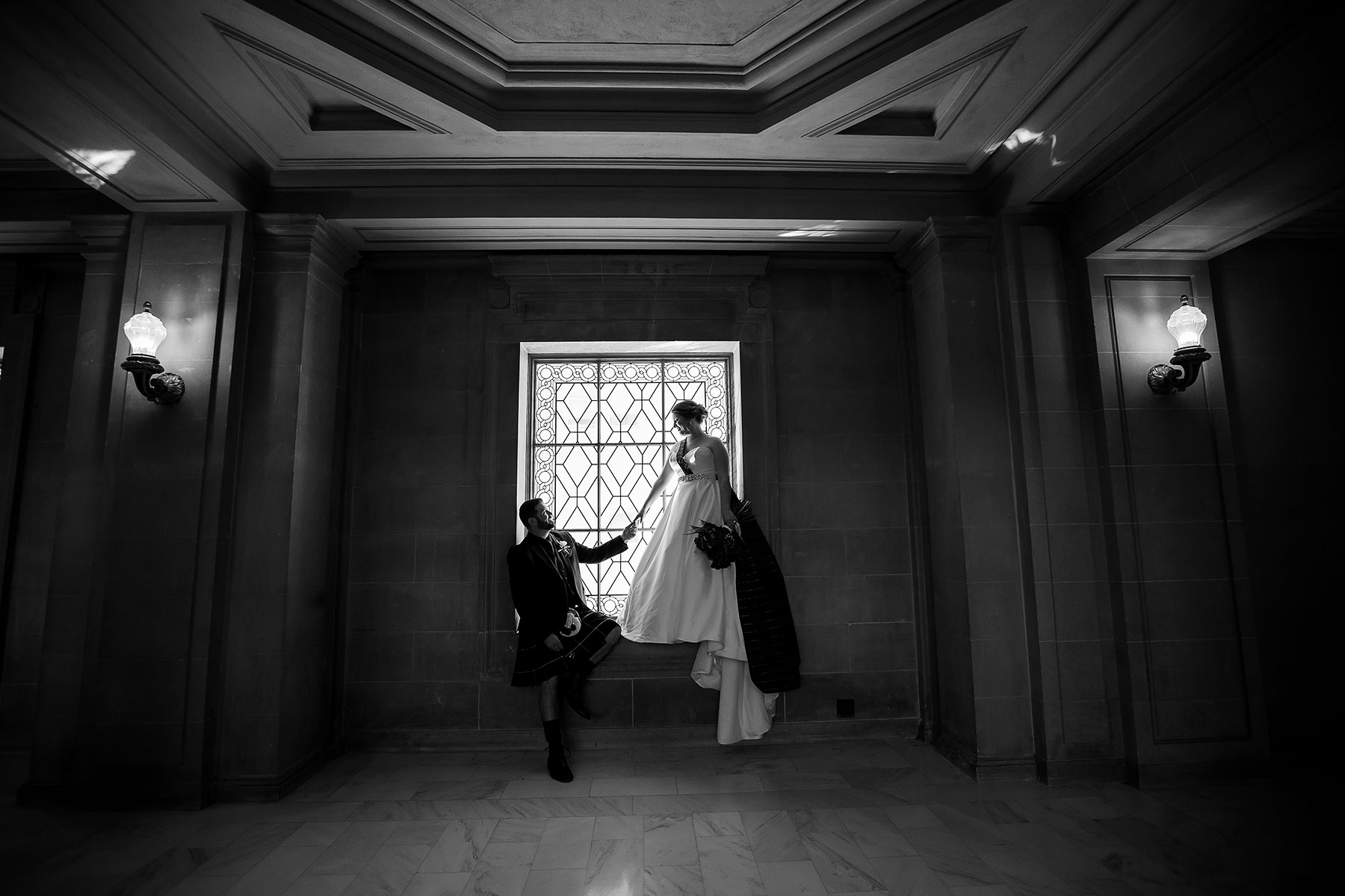 A bride and groom standing in a gorgeous window in San Francisco's Iconic City Hall. A beautiful black and white image of the Bride and Groom