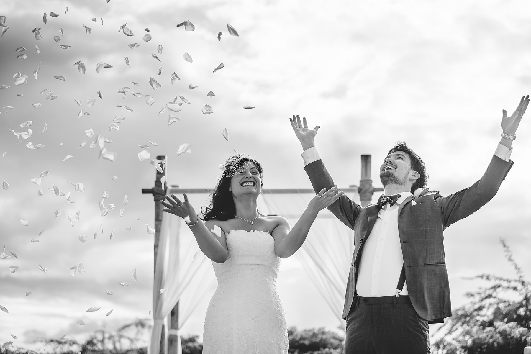 Bride in Groom tossing rose petals in the air, laughing and enjoying their wedding day. A black and white image taken by Tiny House Photo.
