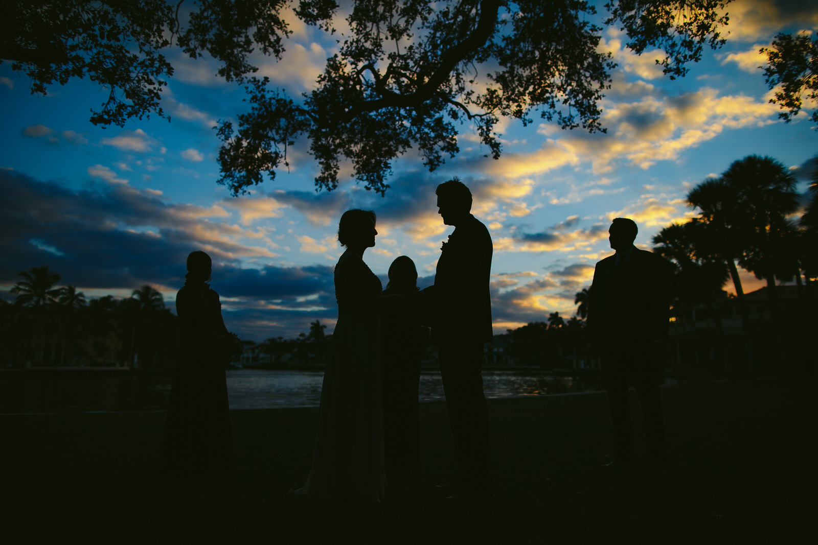 Gorgeous skies during a sunset ceremony in Downtown Fort Lauderdale. Blue skies and silhouettes of bride groom and wedding party can be seen.